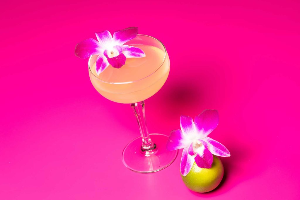 a cocktail in a margarita glass against a bright pink background