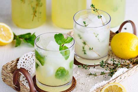 Two glasses of homemade lemonade on a tray with mint and thyme garnish